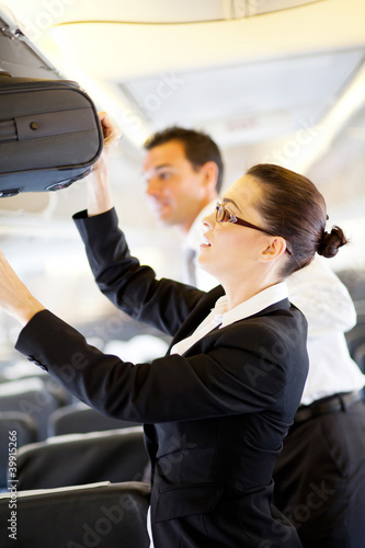 friendly flight attendant helping passenger with luggage