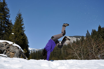 Young woman doing a cartwheel in the snow