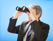Senior businessman looking through binoculars