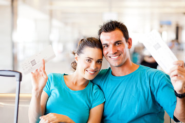 happy young couple with boarding pass at airport
