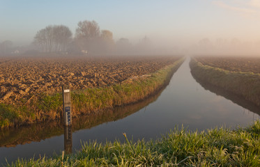 Agricultural landscape with a ditch on a foggy morning