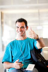 happy young traveller giving thumb up at airport