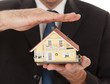 Businessman holding model of a house in hands