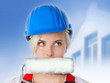 Young woman with building-site helmet and paint roller