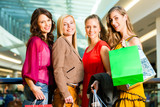 Four female friends shopping in a mall