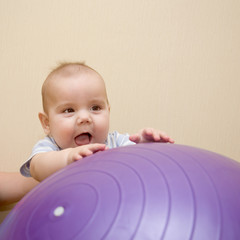 Beautiful baby playing with a big gymnastic ball.