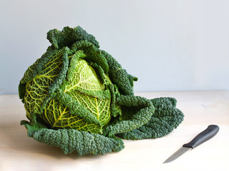 Head of green cabbage with a vegetable knife in the kitchen
