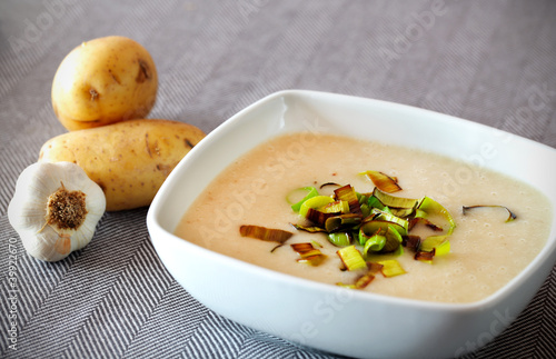 Creamy potato soup with fried leek as an hearty meal