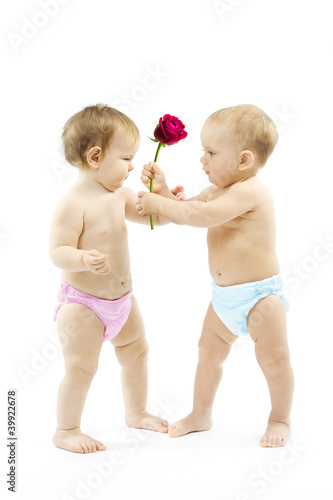 Baby boy present rose flower to a baby girl. Children wear color