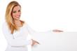 Attraktive junge Frau deutet auf weißes Schild