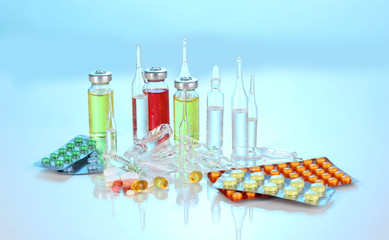 Tablets and ampoules on blue background