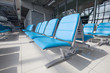row of blue chair at airport
