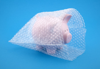 Piggy bank in bubble wrap, protect your money
