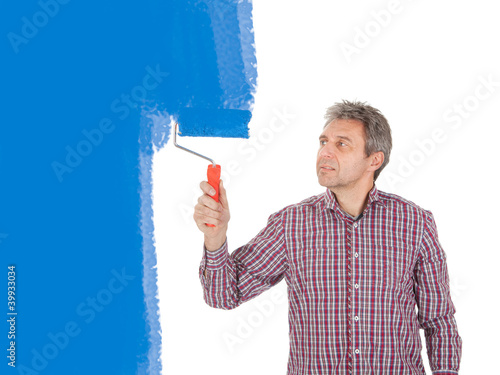Senior adult painting wall in blue
