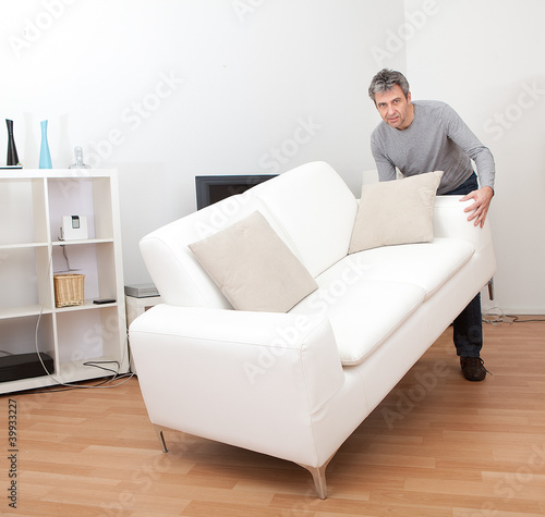 Senior man moving sofa