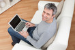Senior man sitting in sofa and using laptop