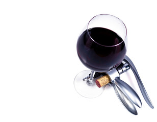 wine glass with red wine and bottlescrew