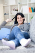 Happy young woman talking on phone lying on a sofa