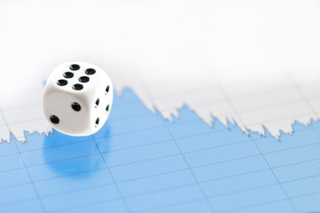White dice on digital screen with financial chart
