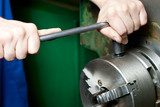 Regulating of turning lathe with hands poster