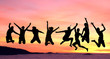silhouette of female friends jumping in sunset