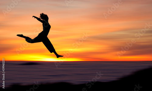 silhouette of girl jumping in sunset