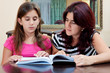 Latin girl reading a book with her beautiful mother