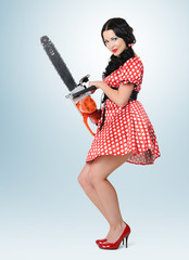 Young sexy pin-up woman with electric saw, concept