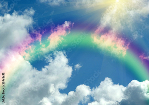 Rainbow in clouds and in blue sky
