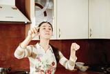 Woman conducting in kitchen