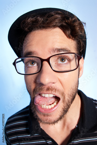 Young man modern nerd wide angle portrait blue background