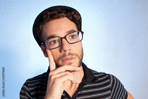 Young man modern nerd thinking wide angle portrait blue