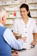 American pharmacist dispensing to senior man