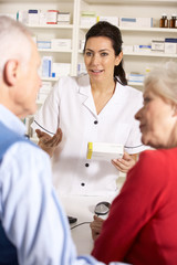 American pharmacist dispensing to senior couple