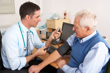 British doctor taking senior man's blood pressure