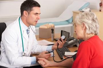 American doctor taking senior woman's blood pressure