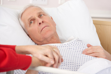 Senior man in hospital bed holding wife's hand