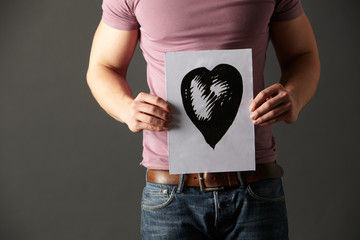 Man holding ink drawing of heart