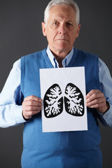 Senior man holding ink drawing of lungs