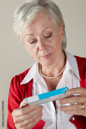 Senior woman looking at prescription drug pack