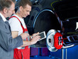 Master mechanic and worker inspecting a car with touchpad