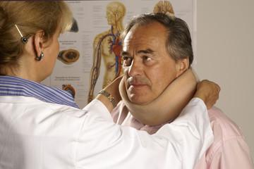 Ärztin legt einem Patienten eine Halskrause an