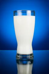 Glass of fresh milk on a dark blue background