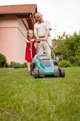 Senior man with lawn mower and child