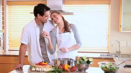 Husband tasting his wife's cooking with a spoon
