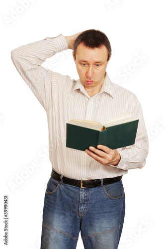 Man with astonishment looks in the book and scratches a nape