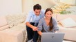 Couple laughing at something on a laptop