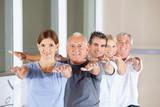 Senioren machen Rückenübungen im Fitnesscenter
