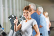 Frau hält Daumen hoch im Fitnesscenter