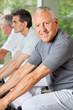 Senioren im Fitnesscenter fahren Rad